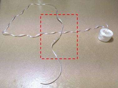 紐で4の字を作った中心に段ボールを置く図