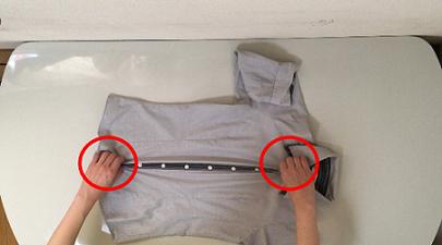 襟の下とスソ部分をつまみ、ぐいっと上に持ち上げている説明写真