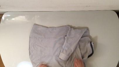 シャツの両腕を内側に折っている説明写真