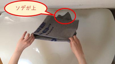 シャツを持ち上げて、 ソデ部分が上側に来るように床の上におろしている説明写真